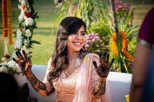 Pretty bride wearing peach lehenga for mehendi