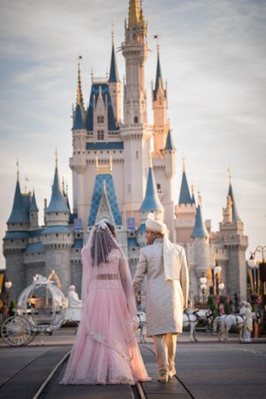 Bride and groom pose infront of Disney World castle at Orlando