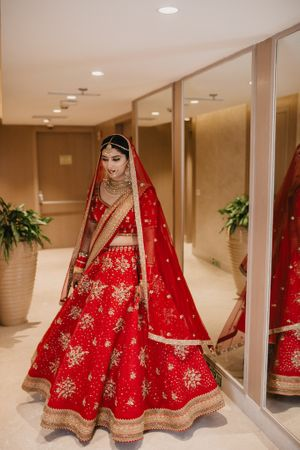 A bride in red lehenga twirling