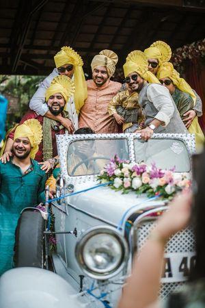 Groom entering venue in vintage car with groomsmen