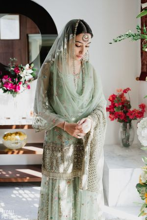 A coy bride to be at her roka ceremony, dressed in a pastel green sharara