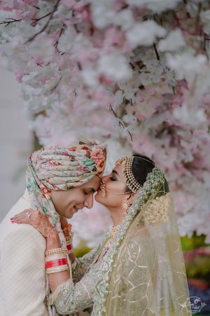 A bride in green kissing her groom on the forehead
