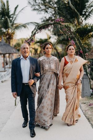 A bride enters with her parents on her wedding day