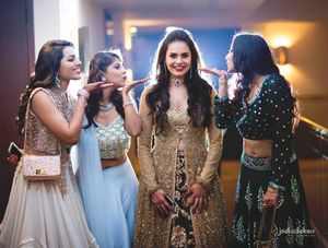 Pretty bride in golden and black anarkali with her bridesmaid
