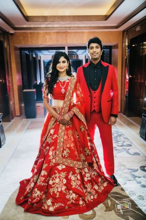 Bride and groom in matching red outfits for reception