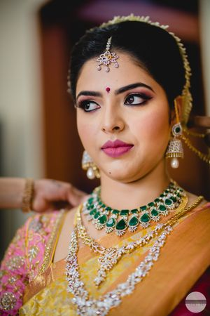 Layered diamond and emerald necklaces for South Indian bride