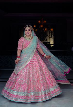 Twirling bride in pretty pink and turquoise lehenga