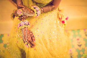 Mehendi hands with yellow and pink haathphool