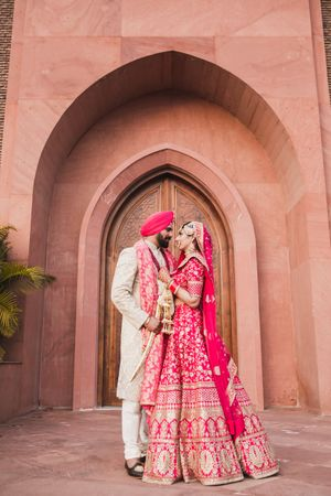 A sikh bride and groom in coordinated outfits pose on their wedding day