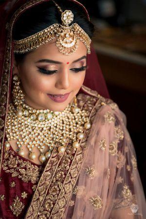 Pretty gold jewellery with maroon bridal lehenga