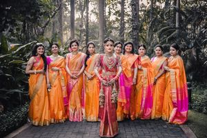 A south indian bride with her bridesmaids in coordinated sarees