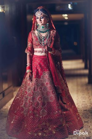 Photo of Bride in red with contrasting layered jewellery and waist belt