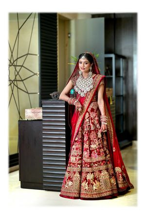 A bride in a maroon lehenga and exquisite jewellery