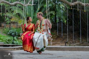 A south indian bride and groom on their wedding day, swinging on a swing