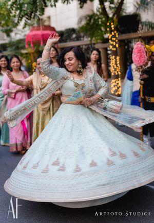 Brides mom dancing in powder blue lehenga