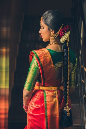 Bridal back shot South Indian bride with green blouse and orange saree