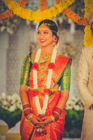 South Indian bridal saree in orange and gold with green blouse