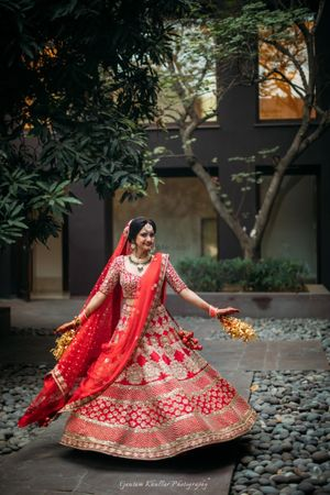 Twirling Sikh bride in red and gold bridal lehenga