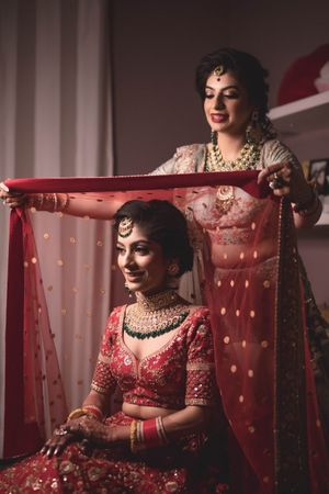 Bride with sister getting ready shot idea