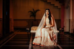 Unique bridal lehenga in white with orange floral motifs