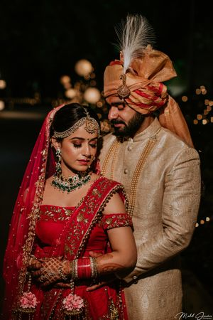A bride in red lehenga with floral kalire ppsing with her husband on their wedding day