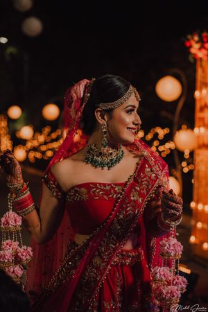 A bride in a red lehenga with offshoulder blouse  and floral kalire on her wedding day