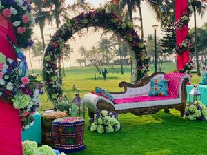 A colorful mehendi seating arrangement with a floral wreath