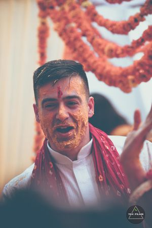 A groom in a white kurta on his haldi day celebrations
