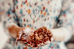 Bride tossing engagement rings with mehendi laden hands