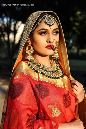 Pretty bride wearing red lehenga with gold and green beads jewelry