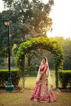 Bride in red poses on her wedding day in a garden