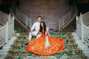 A bride in orange lehenga with her groom