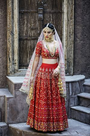 A bride in red poses on her wedding day
