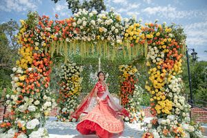 A bride in red twirls infront of her floral mandap
