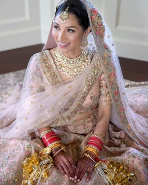 Bride in a light pink and gold lehenga with kaleere
