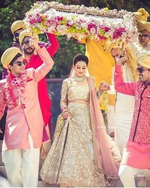 A bride enters under a phoolon ki chaadar with her brothers
