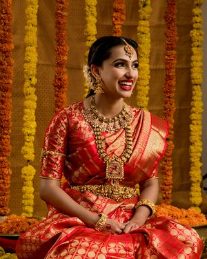 A south Indian bride in a jewel-tone kanjeevaram and stunning temple jewellery
