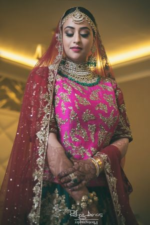 Bride in pink and green lehenga on her wedding day
