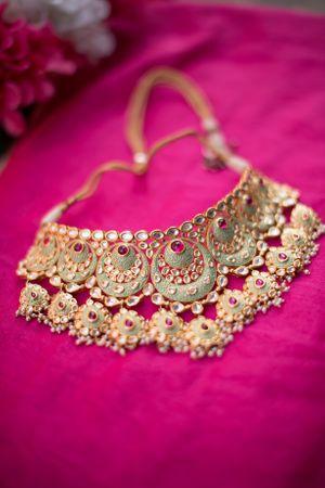 Enamel work necklace against pink backdrop