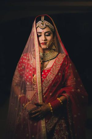 A bride in red lehenga wearing double dupatta