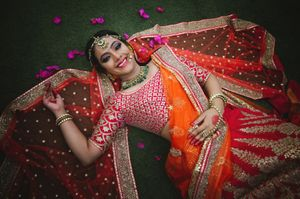 Bridal portrait idea with bride posing in orange dupatta