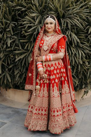 Bride in red and gold lehenga outdoors