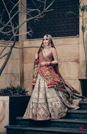 A Sikh bride in a metallic color lehenga wearing kaleere and antique jewellery