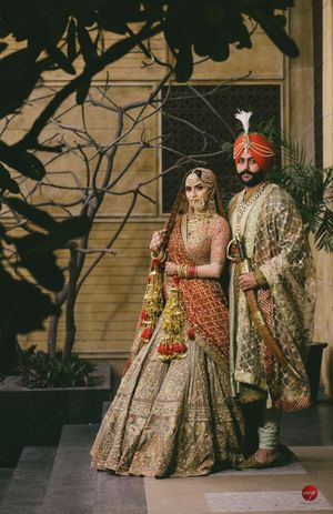 A sikh bride and groom posing together on their wedding day