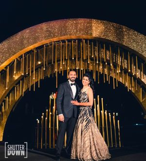 Photo of Glam couple portrait on sangeet with gold decor