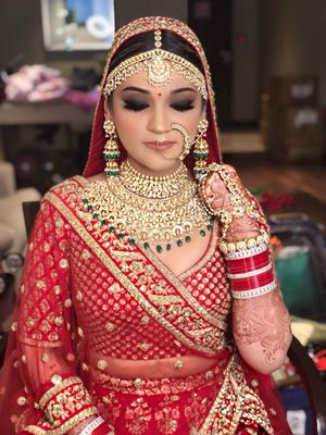 Pretty bride wearing red lehenga with gold jewellery for wedding
