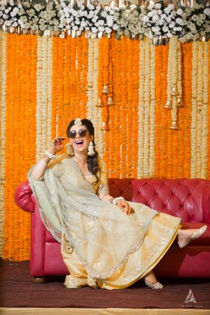 A bride to be poses on her mehendi in front of a marigold decor