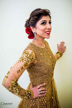 Blingy gold anarkali with red roses in a bridal hairstyle