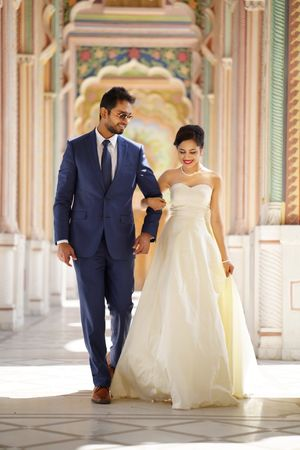Beautiful outdoor couple shot with bride in sweetheart neckline gown and groom in royal blue suit