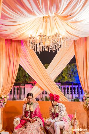 Peach mandap with drapes and chandeliers
